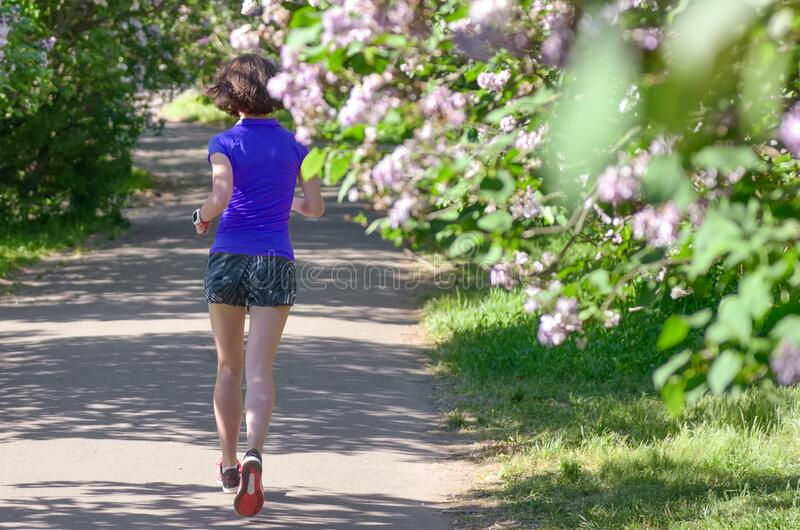 Active woman runner running in spring park with lilac blossom, morning run outdoors, fitness jogging healthy lifestyle royalty free stock photos