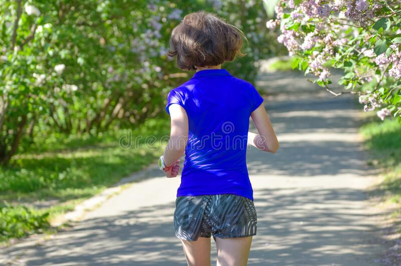 Active woman runner running in spring park with lilac blossom, morning run outdoors, fitness jogging healthy lifestyle stock photos