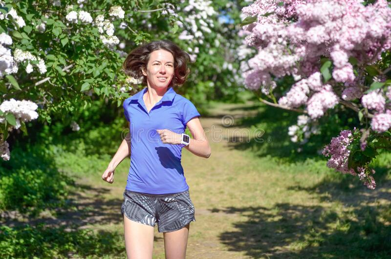 Active woman runner running in spring park with lilac blossom, morning run outdoors, fitness jogging healthy lifestyle royalty free stock image