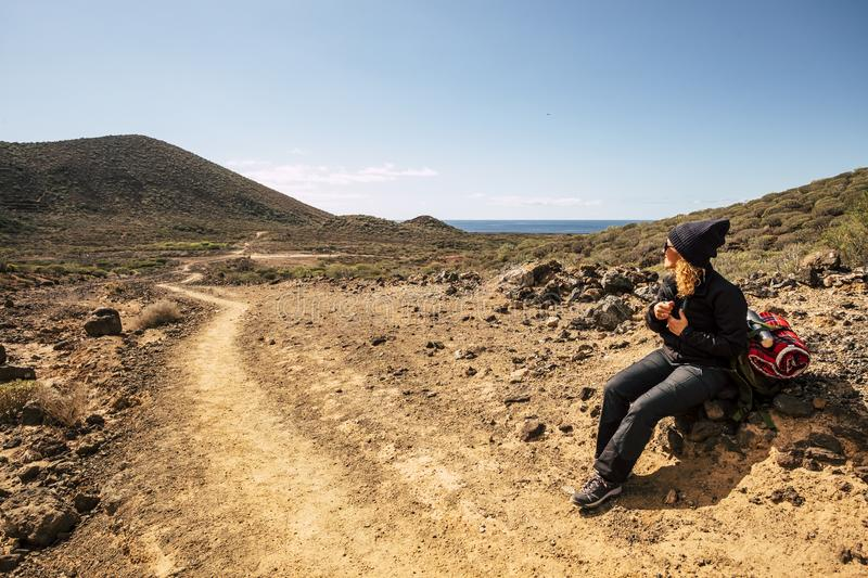 Active woman sit down on the rocks resting during a trekking activity in the mountains - ocean and sky in background, scenic place stock images