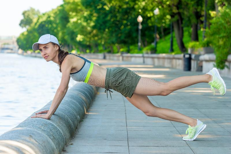 active woman with a sports figure doing pushups on the city waterfront stock image