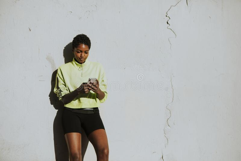 Active woman standing by a white wall stock image