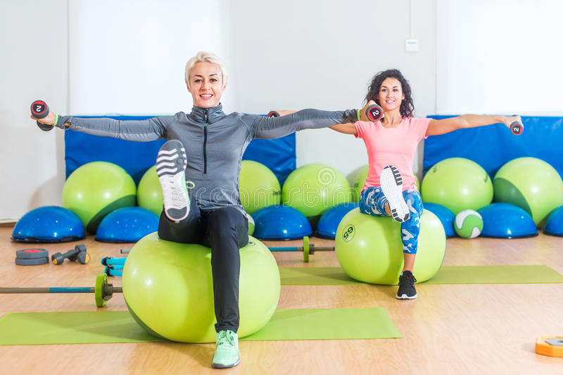 Active women sitting on exercise balls lifting legs and doing dumbbell lateral raise. Two mature females working out in stock photos