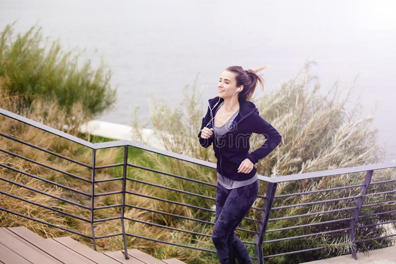 View at active young beautiful woman running by river royalty free stock image