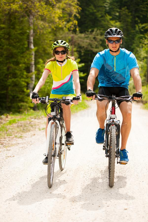 Free ACTIVE Young Couple Biking On A Forest Road In Mountain On A Spring Day Stock Photography - 106933182