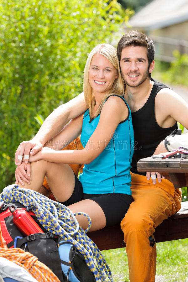 Active young couple climbing gear relax terrace. Portrait backpack active young couple sitting by terrace climbing gear stock photography