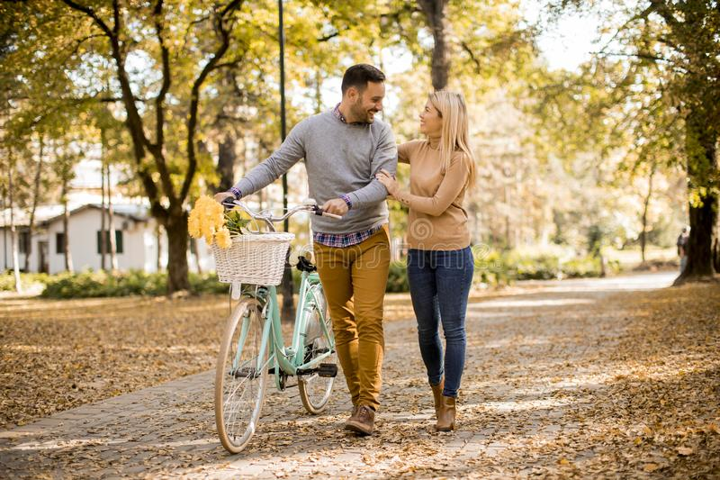 Active young couple enjoying romantic walk with bicycle in golden autumn park royalty free stock images