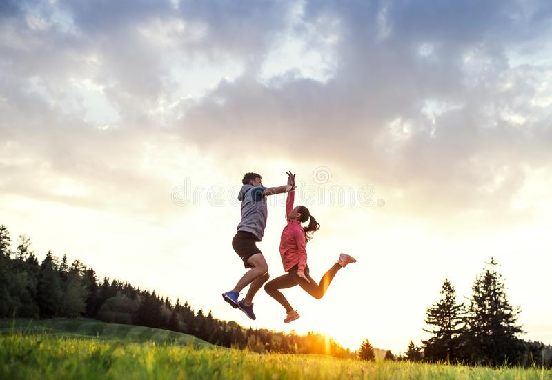 Active young couple jumping after doing exercise in nature at sunset. royalty free stock image
