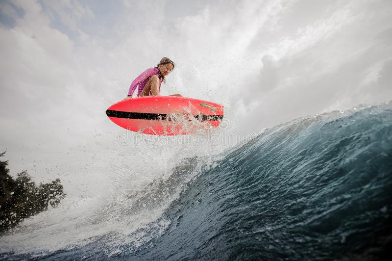 Active young girl jumping on the orange wakeboard stock photography