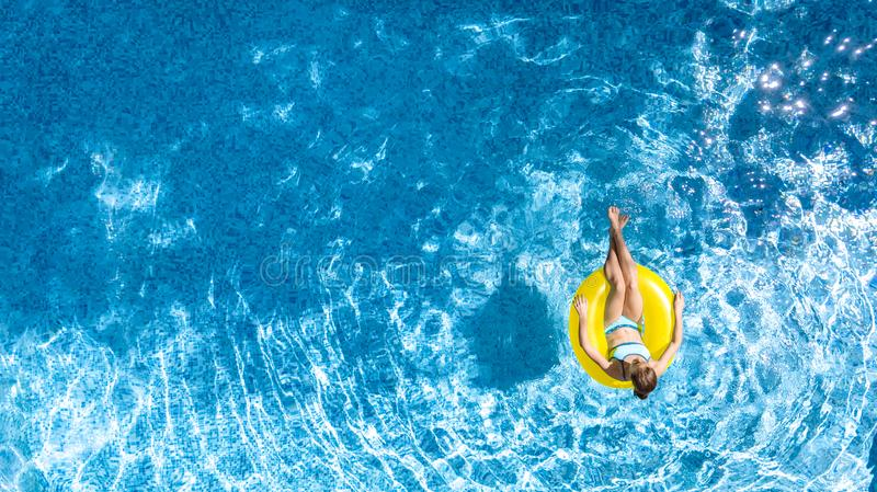 Active young girl in swimming pool aerial top view from above, child relaxes and swims on inflatable ring donut, fun in water stock photography