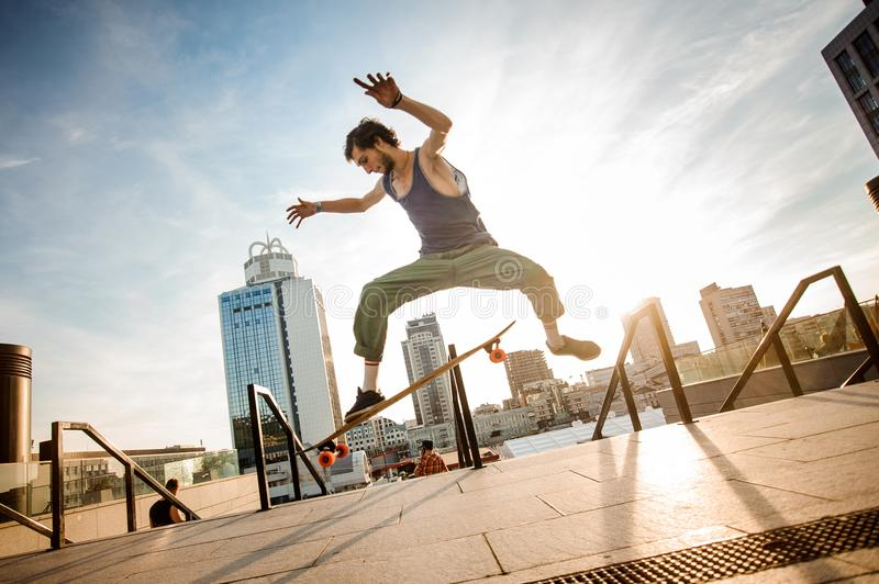 Active young man jumping on skateboard against the city building royalty free stock photo