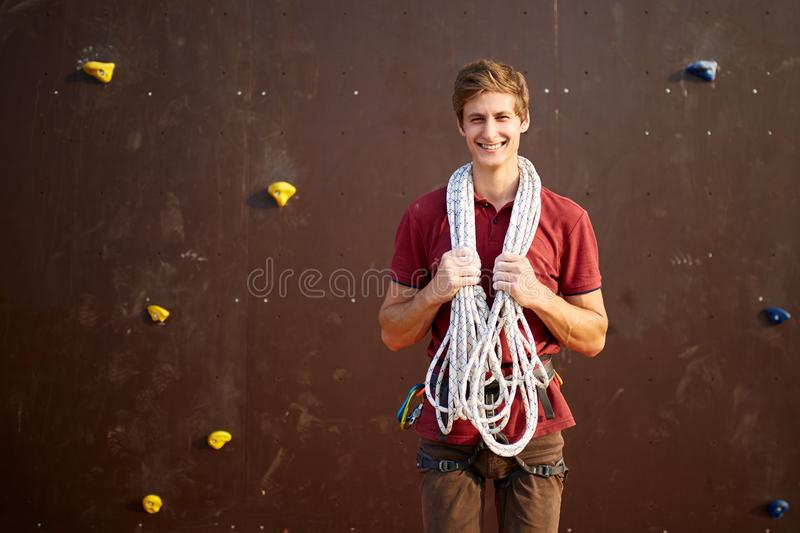 Active young man in sportswear standing with rope on shoulders against artificial training climbing wall. Smiling royalty free stock image