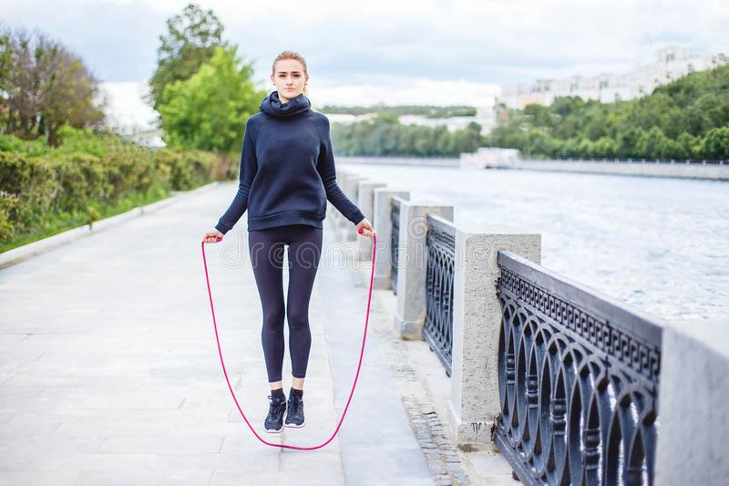 Active young woman jumping with skipping rope outdoors. Active young woman jumping with skipping rope outdoors royalty free stock image