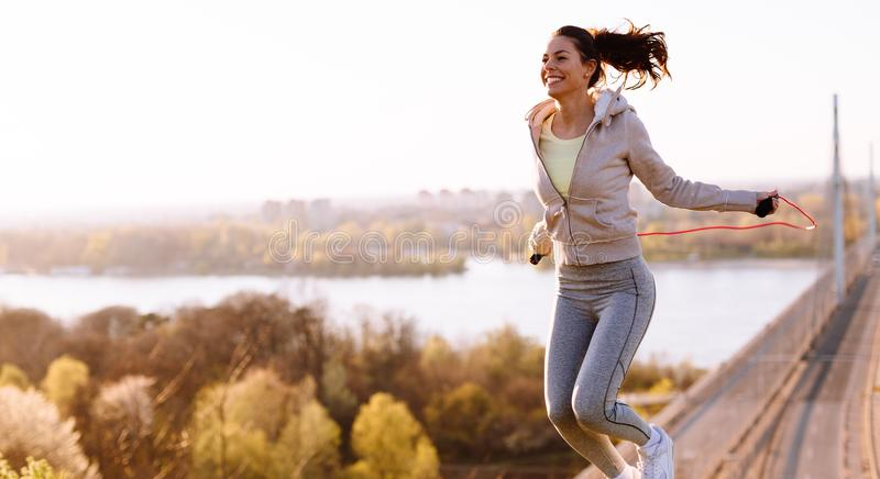 Active woman jumping with skipping rope outdoors. Active young woman jumping with skipping rope outdoors stock photos