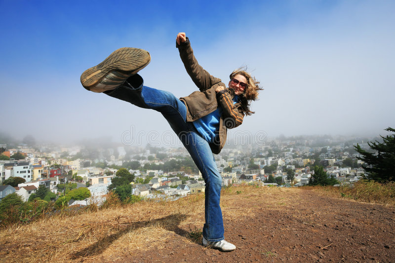 Active young woman outdoors. Young woman fooling around doing high kick ontop of the Kite Hill, San Francisco, California, USA stock images
