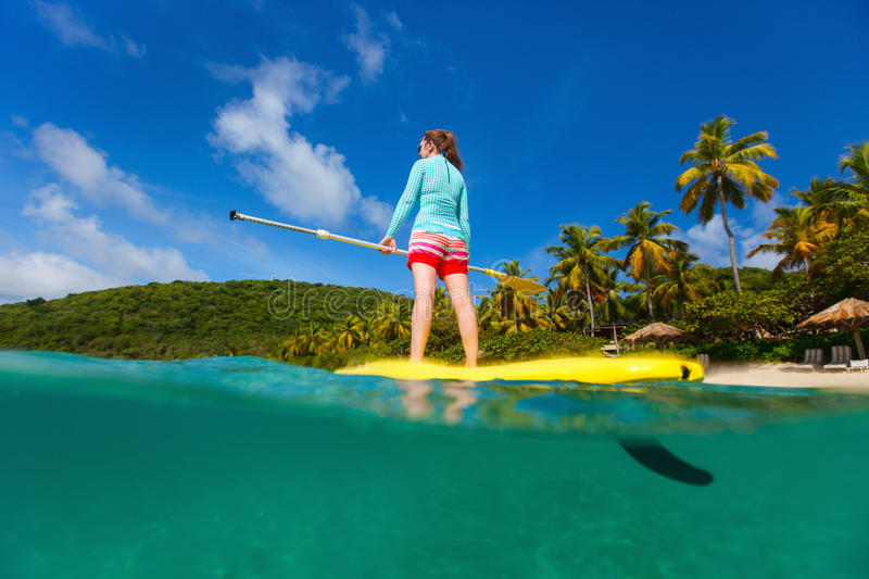 Active young woman on vacation. Split underwater photo of active young woman on tropical beach vacation paddling on stand up board stock images