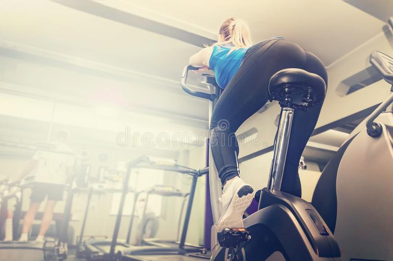 Active young woman working out, doing sport biking in the gym for fitness. Sporty girl training in club. Slim body weight loss con royalty free stock photography