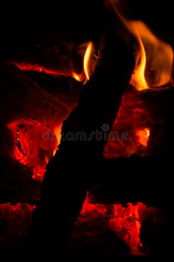 Actively smoldering embers of fire. Background of burning hot coals. Flicker of burning coals at night royalty free stock image