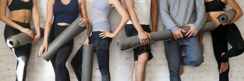 Activewear de port de personnes de groupe tenant des tapis de yoga se tenant près du mur image stock