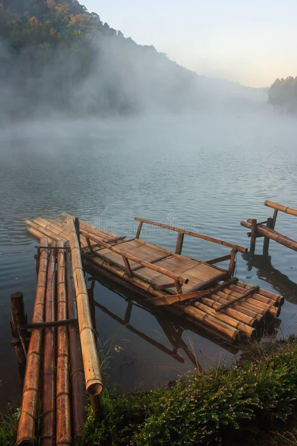 Actividad al aire libre respetuosa del medio ambiente, bambú flotante que transporta en balsa por la mañana en el lago sereno con imágenes de archivo libres de regalías