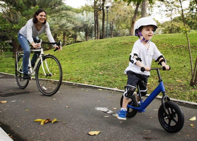Actividad del fin de semana del día de fiesta de la familia que monta en bicicleta imagenes de archivo