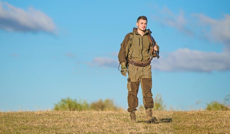 Actividad masculina de la afici?n Arma o rifle del arma de la caza El cazador del hombre lleva el fondo del cielo azul del rifle  imágenes de archivo libres de regalías