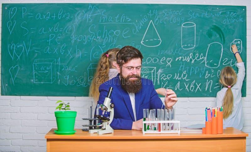 Actividades de la investigaci?n y de entrenamiento Profesor y alumnos elementales en laboratorio de investigaci?n Profesor de cie imagen de archivo