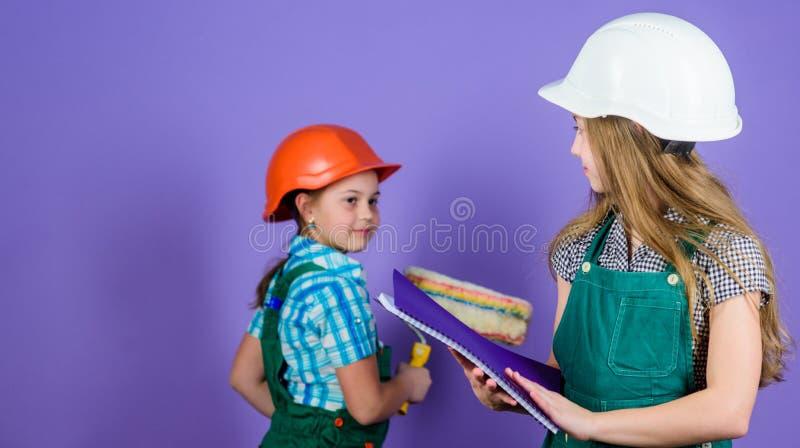 Actividades de las mejoras para el hogar Muchachas de los ni?os que planean la renovaci?n Repinte las paredes Movimiento en el nu fotos de archivo