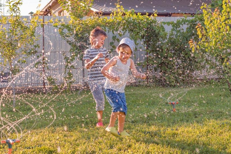 Actividades del verano El jugar de los ni?os al aire libre con el sistema de riego autom?tico de la planta Muchacho sonriente que imágenes de archivo libres de regalías