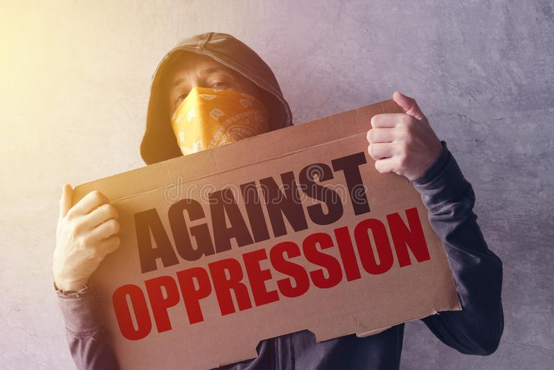 Activist protesting against oppression. Hooded male person with scarf over face holding a banner with statement stock photos