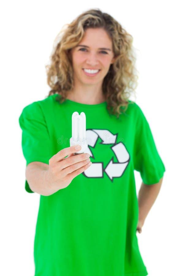 Activista ambiental alegre que sostiene una bombilla foto de archivo libre de regalías