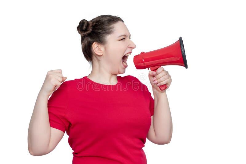 Activista de la mujer joven en camiseta roja que grita en un megáfono, aislado en el fondo blanco imagenes de archivo