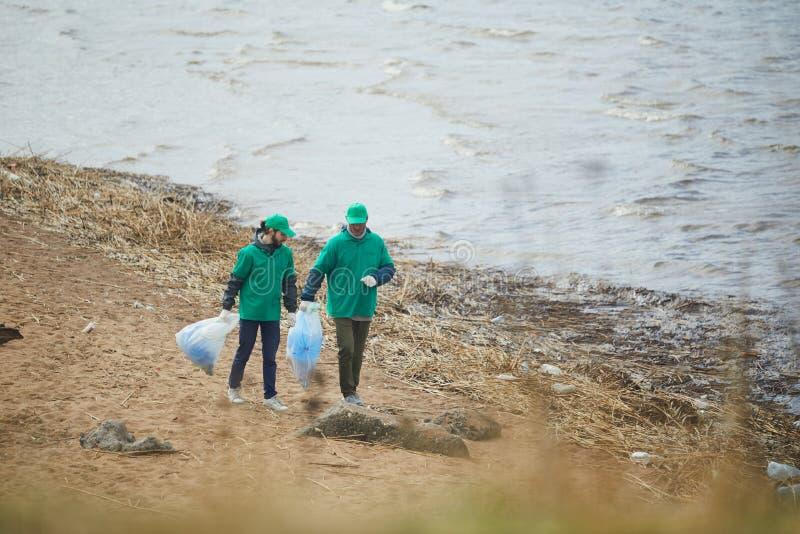 Activisten die met vuilniszakken op kust lopen royalty-vrije stock foto's