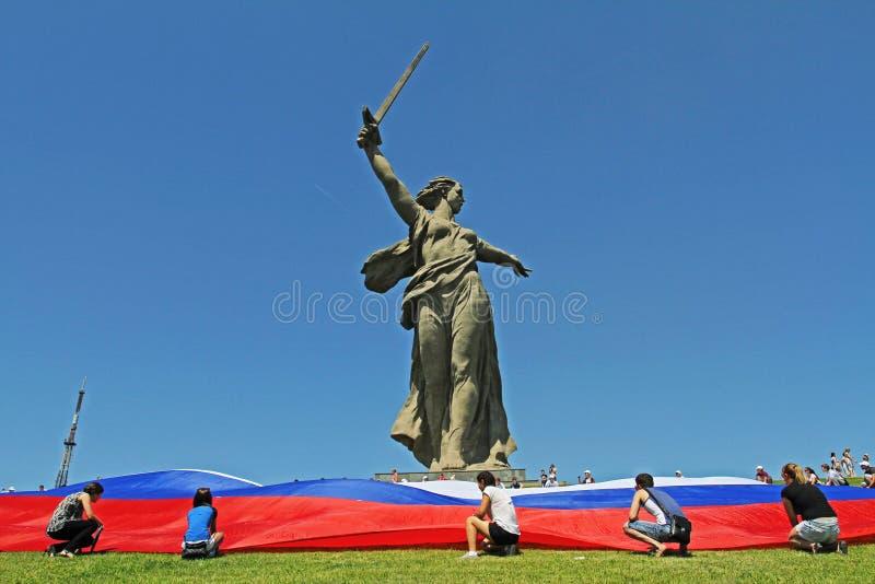 Activisten unfurl een grote Russische vlag in Dag van Rusland bij de voet van het monument van de Vraag van het Vaderland op Mama stock fotografie