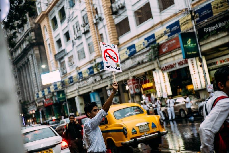 """Activistes d'étudiant indiens exigeant paisiblement pour le """"silence, aucun klaxon """"sur la route avec les taxis jaunes à l' images stock"""
