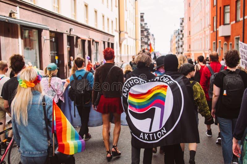 Activistes d'Antihomophobe dans les masques sur le festival de fierté de Helsinki sur la rue photo libre de droits