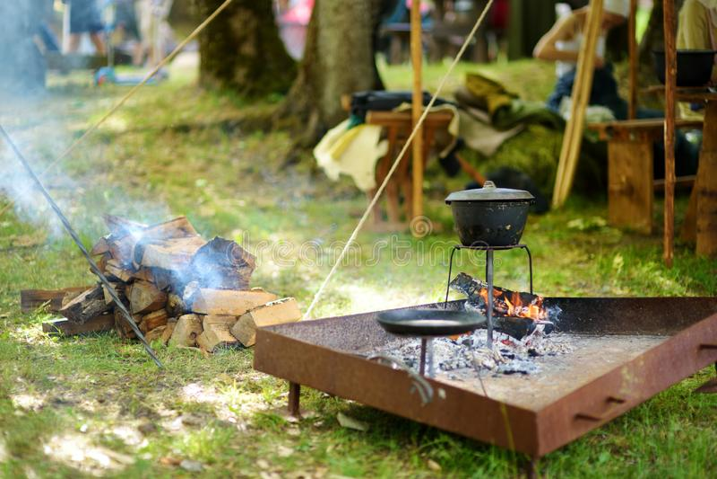 Activistes historiques de reconstitution préparant la nourriture au-dessus d'un feu ouvert pendant le festival médiéval annuel, j photographie stock libre de droits