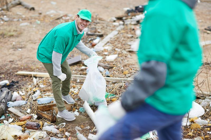Activists collecting garbage. Cheerful activists in green uniform collecting garbage on polluted place stock photo