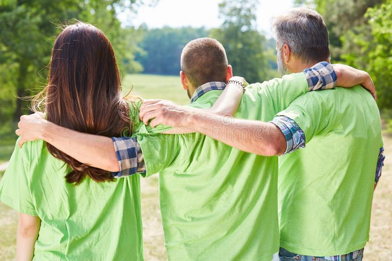 Activists in green shirt hug each other. Three environmentalists or activists in green shirt hugging each other stock photo