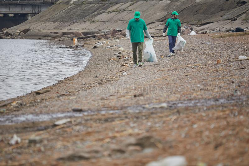 Men collecting garbage on coast. Activists in green uniform walking on polluted shore and collecting rubbish to bags stock image