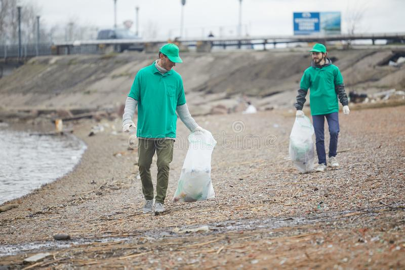 Volunteers walking with litter bags. Activists in green uniform walking on shore and cleaning it from garbage royalty free stock image