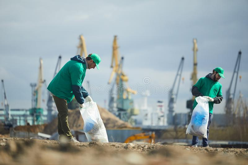Activists picking garbage on site. Two volunteers in green uniform picking garbage on construction site royalty free stock photography