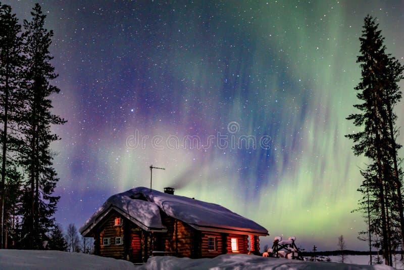 Activité arctique polaire d'Aurora Borealis de lumières du nord au-dessus de cottage en bois en hiver Finlande, Laponie images libres de droits