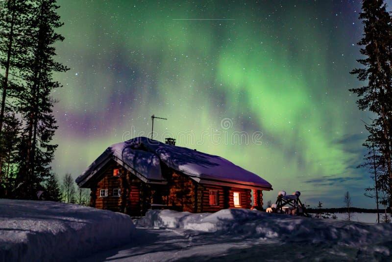 Activité arctique polaire d'Aurora Borealis de lumières du nord au-dessus de la maison en bois en hiver Finlande, Laponie photographie stock
