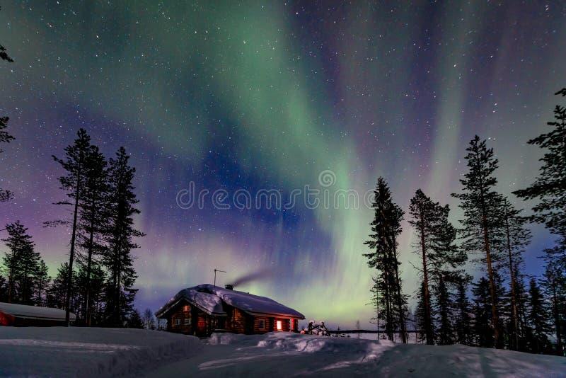 Activité arctique polaire d'Aurora Borealis de lumières du nord au-dessus de maison en bois en hiver Finlande, Laponie images stock