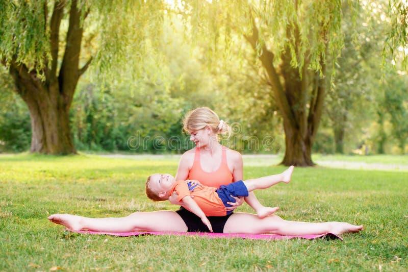 Activité parentale familiale Jeune mère caucasienne avec enfant garçon en bas âge faisant de l'exercice yoga fitness en plein air photographie stock libre de droits
