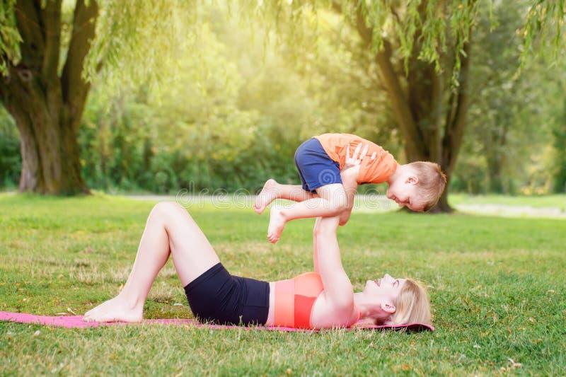 Activité parentale familiale Jeune mère caucasienne avec enfant garçon en bas âge faisant de l'exercice yoga fitness en plein air photo libre de droits