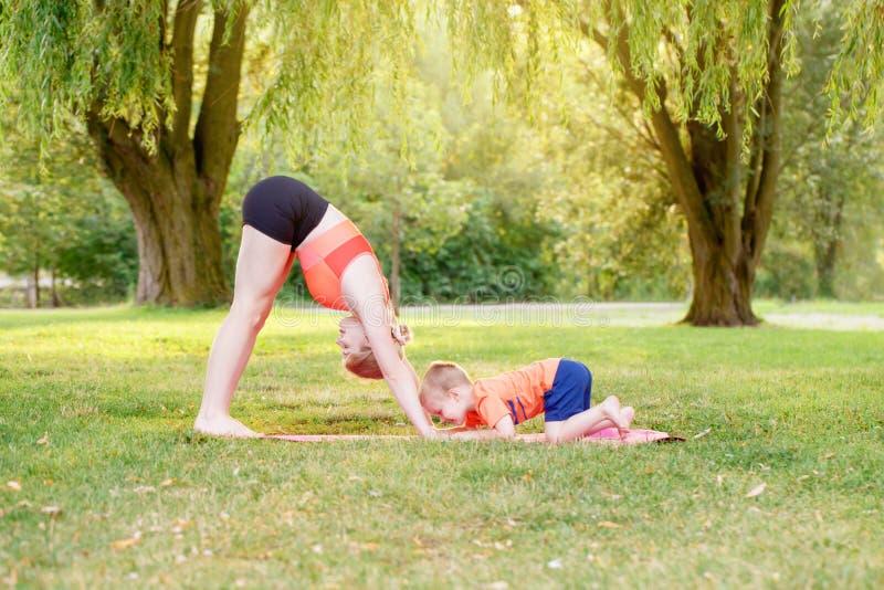 Activité parentale familiale Jeune mère caucasienne avec enfant garçon en bas âge faisant de l'exercice yoga fitness en plein air photographie stock