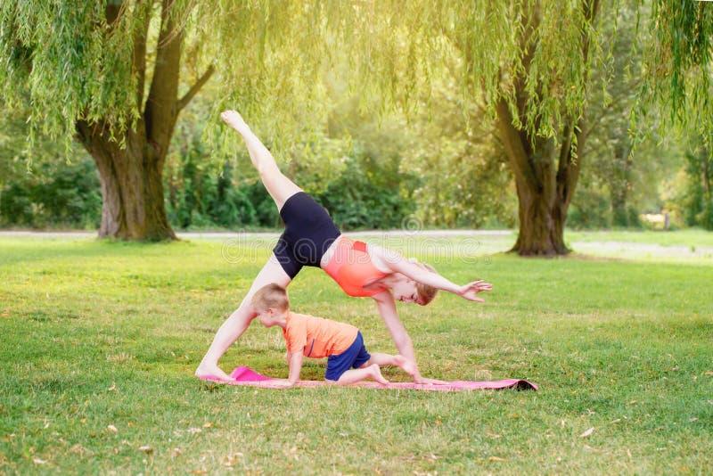 Activité parentale familiale Jeune mère caucasienne avec enfant garçon en bas âge faisant de l'exercice yoga fitness en plein air images libres de droits