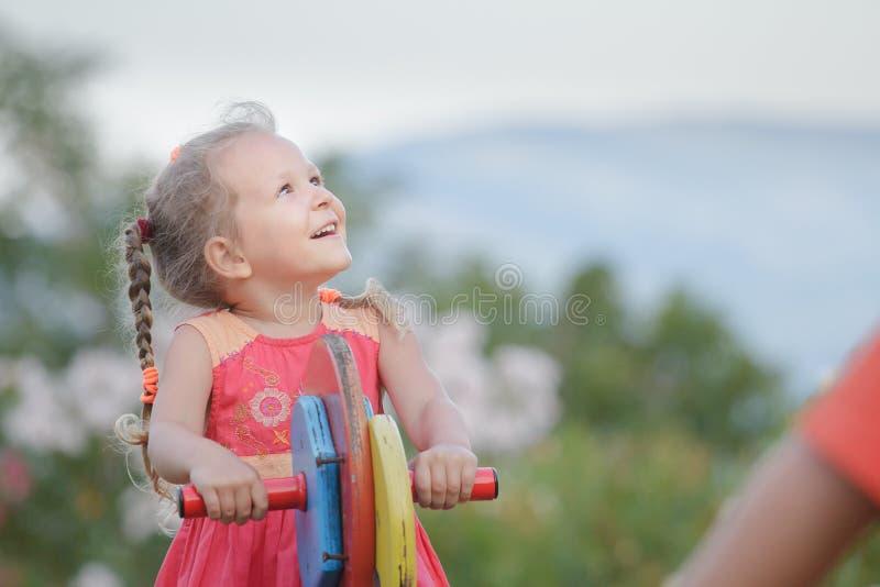 Activité récréationnelle de peu de fille d'enfant balançant sur l'équipement en bois de terrain de jeu dehors photos stock